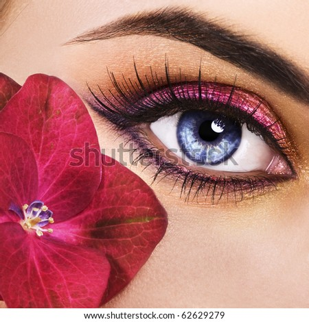 Woman beautiful eye with pink flower - stock photo