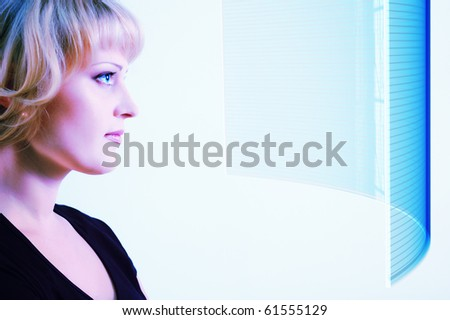 woman beautiful looking at screen over light blue background - stock photo