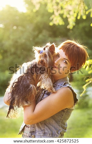 woman beautiful young happy holding small dog in summer day walks in park