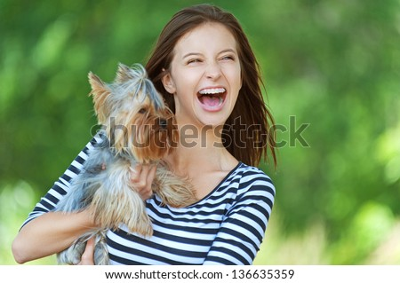 woman beautiful young happy with long dark hair in striped sweater holding small dog - stock photo