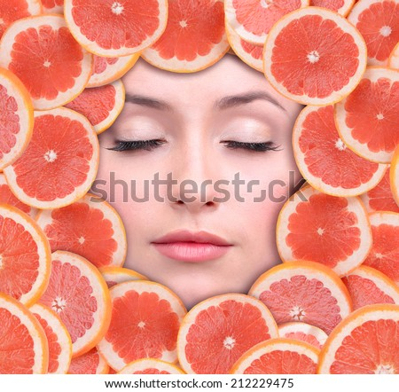 Woman beauty face with grapefruit frame, close-up - stock photo