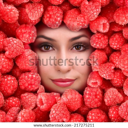 Woman beauty face with raspberry frame, close-up - stock photo