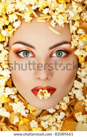 woman beauty face with unhealth eating fast food popcorn potato chips rusk frame - stock photo