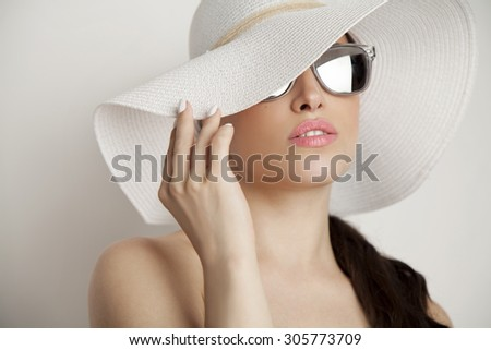 woman beauty portrait with summer white hat and sunglasses, studio