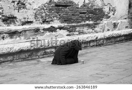 Woman begging in Venice (Italy). Aged photo. Black and white. - stock photo