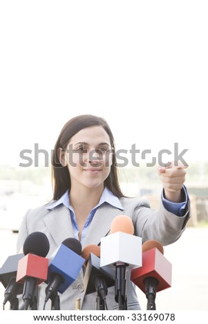 woman behind bank of microphones - stock photo
