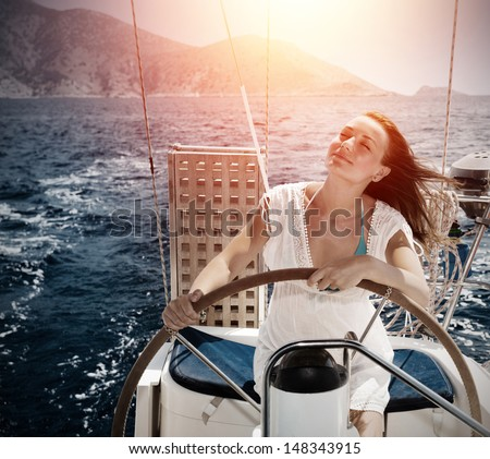 Woman behind the wheel yacht, enjoying sea nature and mountains landscape, active sailor girl, female driving luxury water transport, summertime concept - stock photo