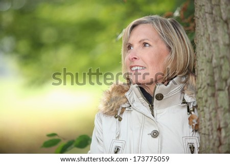 Woman behind tree - stock photo