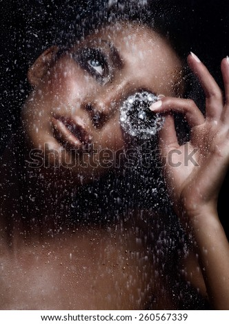 Woman behind wet window in snowfall holding a diamond brooch.