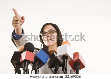 woman behing a bank of microphones pointing - stock photo