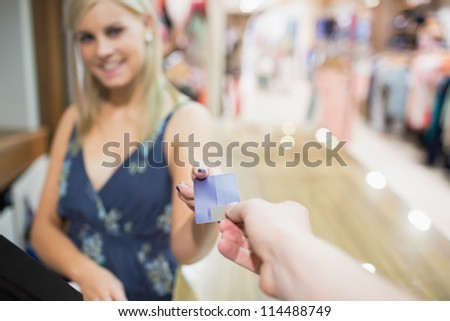Woman being handed credit card in clothing store - stock photo