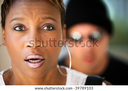 Woman being stalked by criminal in sunglasses and ski hat - stock photo