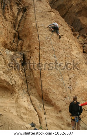 Woman belaying a climber on rock face,		Smith Rock State Park, 	Central Oregon - stock photo