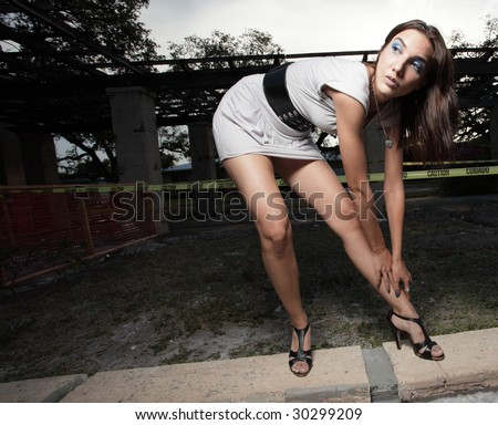 Woman bending over and glancing away - stock photo
