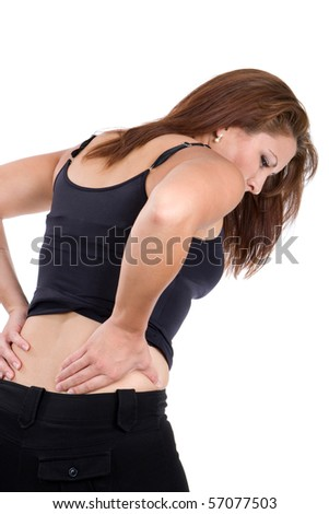 Woman bends over in pain rubbing her lower back as a result of a spinal injury accident. - stock photo
