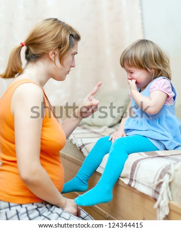 Woman berates crying child in home interior - stock photo