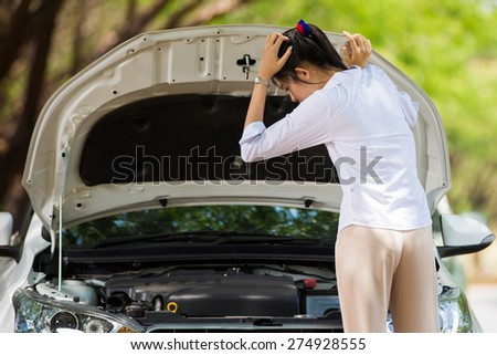 Woman beside her broken car She opened the hood to see the damage - stock photo
