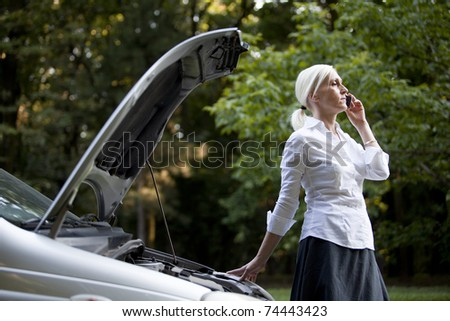 Woman besides her broken car talking on the cell phone - stock photo