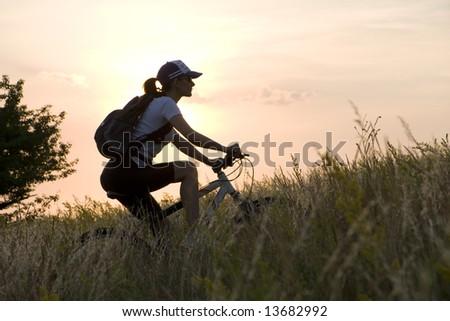 woman biker on a meadow in sunset - stock photo