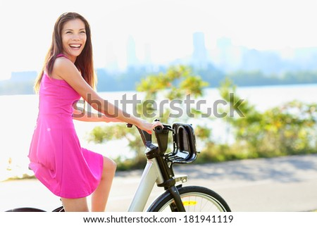 Woman biking in city park on bicycle. Happy girl on bike cycling outdoors in summer smiling of joy during outdoor activity. - stock photo