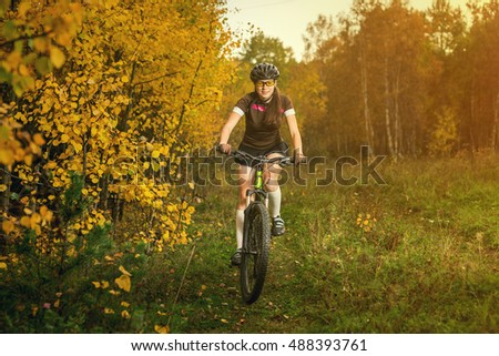 Woman biking in yellow autumn forest on a green meadow