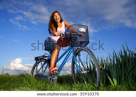 Woman biking under deep blue sky in the countryside of Jutland, Denmark during summer. Beautiful happy woman. - stock photo