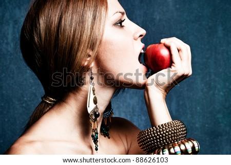 woman bite an apple, profile, studio shot - stock photo