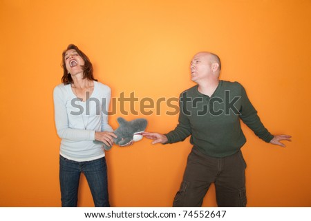 Woman bites bald man's finger with shark toy - stock photo