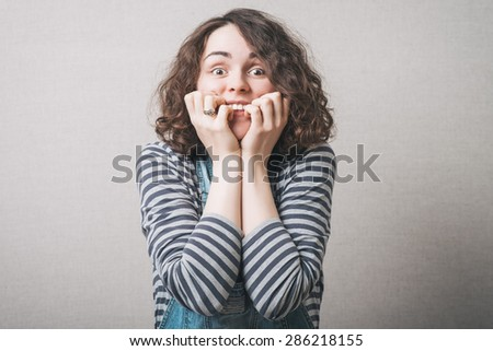 Woman bites his nails from the experience. On a gray background. - stock photo