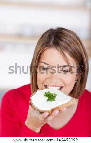 Woman bites into a slice of bread with butter and a heart made with cress - stock photo