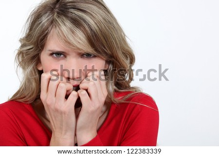 Woman biting her nails in fright