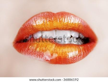 woman biting lip with gold orange lipstick - stock photo