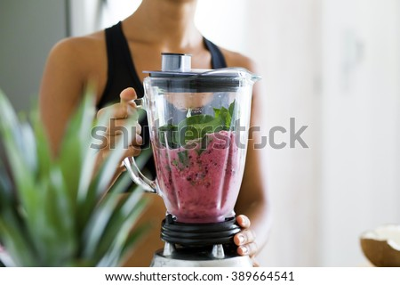 Woman blending spinach, berries, bananas and almond milk to make a healthy green smoothie - stock photo