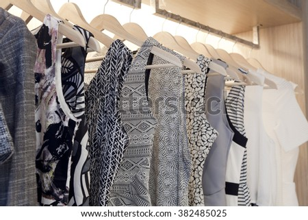 woman blouses and dress are hanging in open wooden wardrobe - stock photo