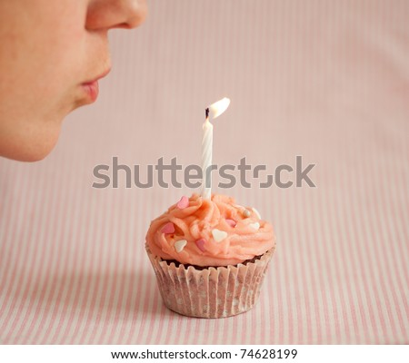 Woman blowing a candle on a pink cupcake