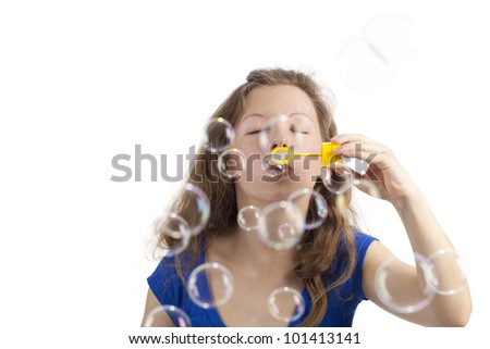 Woman blowing bubbles with closed eyes - stock photo