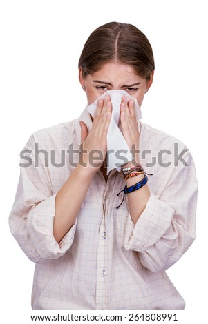 Woman blowing her nose in a white tissue trying to escape the virus contagion, isolated on white
