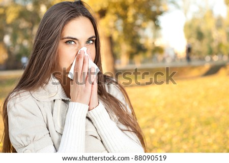 woman blowing her nose in background autumn park
