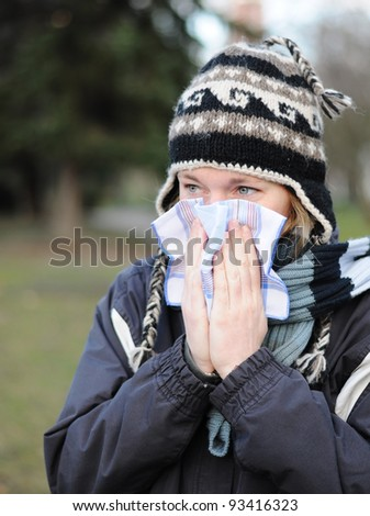 Woman blowing her nose into tissue, winter outdoor portrait