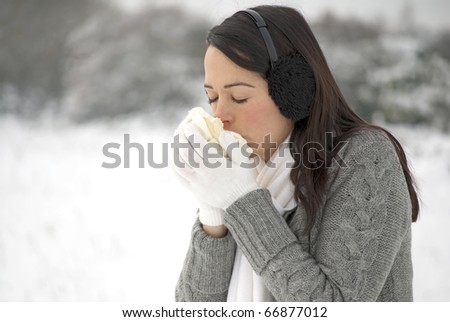 Woman blowing her nose outside in the cold - stock photo