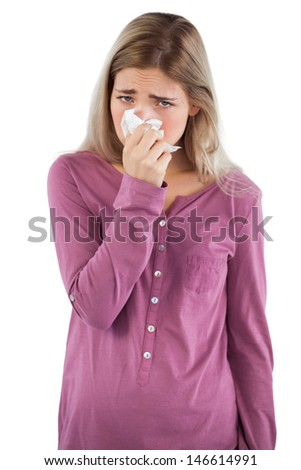 Woman blowing her nose while looking at the camera on a white background - stock photo