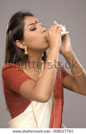 Woman blowing into a shell - stock photo