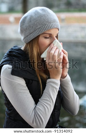 Woman blowing into tissue - stock photo
