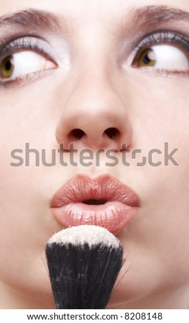 woman blowing loose powder from thick black brush - stock photo