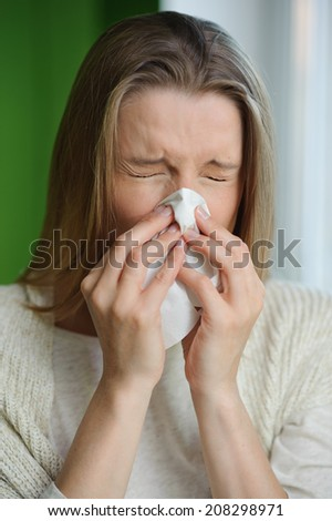 Woman blowing runny nose - Cold flu illness - vertical image - stock photo
