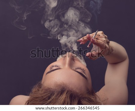 Woman blowing smoke against black background. - stock photo