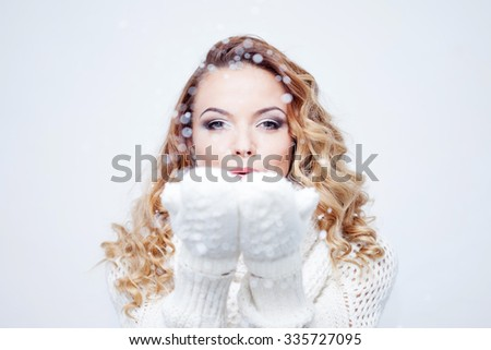 Woman Blowing Snow, girl in  warm knitted scarf and gloves, portrait on  white background, place for your text - stock photo