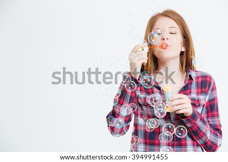 Woman blowing soap bubbles isolated on a white background
