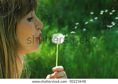 Woman blows on dandelion