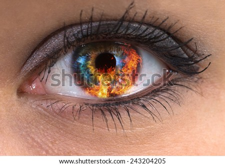 woman blue eye with burning fire in it - stock photo
